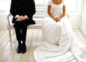 view of a bride and groom sitting on a bench
